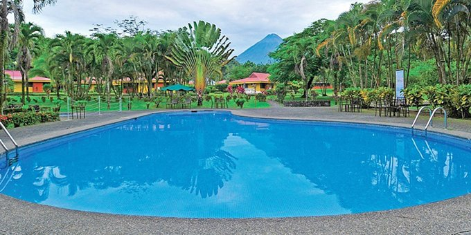 Arenal Country Inn is a 3 star hotel located just outside of La Fortuna, in the shadow of the majestic Arenal volcano. The hotel offers guests tranquility of nature in a beautiful country setting.  Guests of Arenal Country Inn will enjoy amenities such as outdoor swimming pool, lounge chairs, bar, restaurant, entertainment area, tour desk, internet access, tropical gardens, volcano views, and parking facilities.