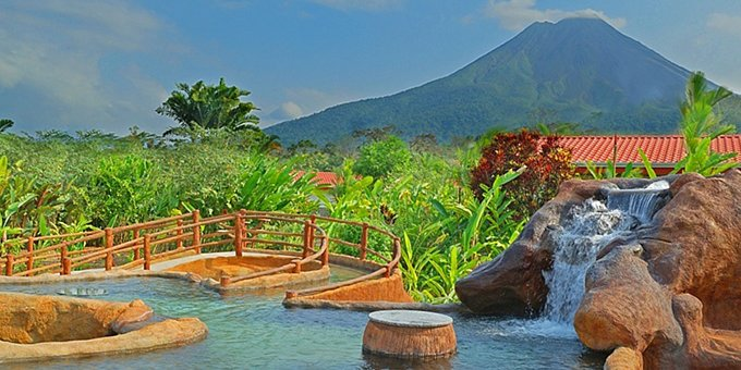 The family-friendly Volcano Lodge, Hotel & Thermal Experience is conveniently located near the base of the magnificent Arenal Volcano. This affordable hot springs resort is surrounded by beautiful tropical gardens and views of Arenal Volcano are spectacular from the cool water swimming pool and thermal springs pool. The lodge also has an onsite restaurant and bar, wet bar, spa, kids pool, and free wireless internet service in some areas.