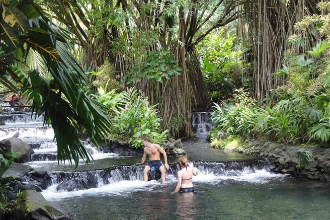 A couple enjoys Tabacon hot springs at the base of Arenal Volcano.